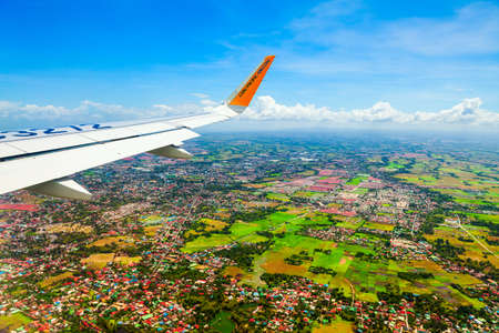 MANILA, PHILIPPINES - FEBRUARY 23, 2013: Cebu Pacific airplane wing above the Manila city suburbs in Philippines