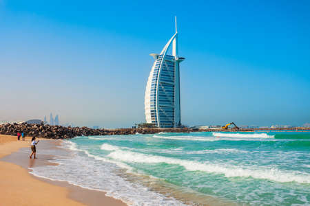 DUBAI, UAE - FEBRUARY 27, 2019: Burj Al Arab luxury hotel and Jumeirah public beach in Dubai city in UAE Редакционное