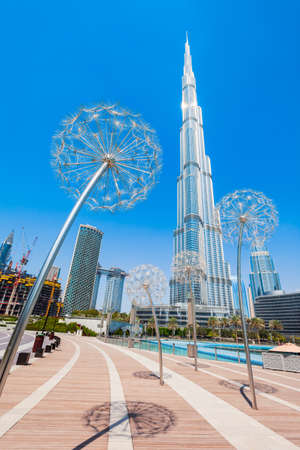DUBAI, UAE - FEBRUARY 26, 2019: Promenade near the Burj Khalifa Tower and Dubai Mall in Dubai city in United Arab Emirates Редакционное