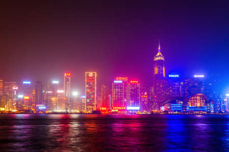 HONG KONG - FEBRUARY 21, 2013: Hong Kong Island skyline viewed from the Victoria Harbour waterfront at night. Hong Kong is a city and special region of China.