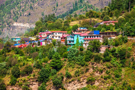 Scenic landscape of the local houses and forested Himalaya mountains in Parvati valley, Himachal Pradesh state in India Фото со стока