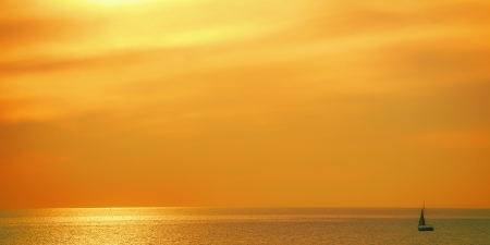 Ship sinking in the golden sunset in the Mediterranean Sea Stock Photo