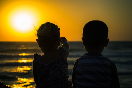 Silhouettes of happy children on a sunset by the sea