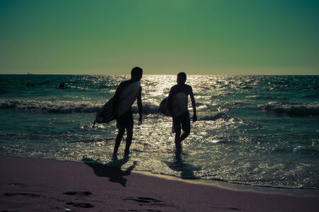 silhouettes of young surfers on the sea