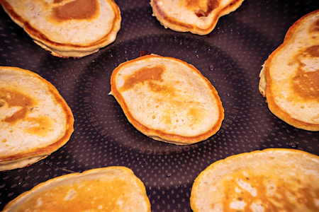 griddle: cooking pancakes in a frying pan closeup