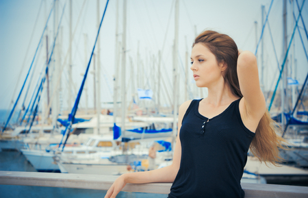 Beautiful young girl on the background of a yacht club
