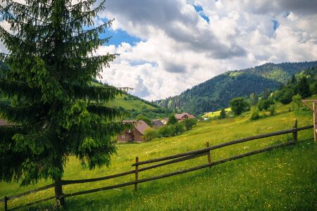 landscape in the Carpathian Mountains with a fence and fir tree in the foreground and houses on the slopes