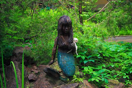 wooden figure: wooden figure of a mermaid in the garden sitting on a rock