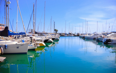 Photo of incredible beauty Harbor Yacht Club with glazed clear sea and blue clouds. Italy. Nettuno.