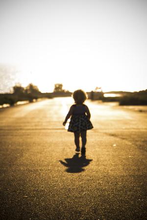 desert highway: little girl flees on the road forward Stock Photo