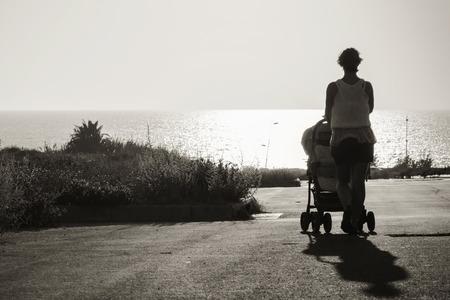 empujando: extiende en la distancia a la madre del mar con el cochecito. foto en blanco y negro Foto de archivo