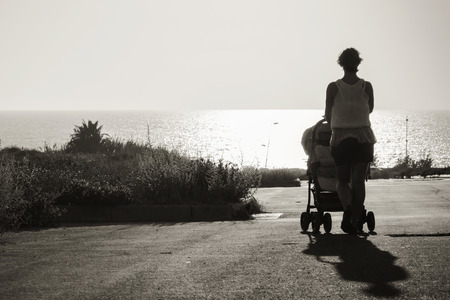 stretching into the distance to the sea mother with stroller. black and white photo 版權商用圖片