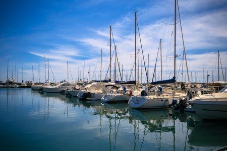 Foto van ongelooflijke schoonheid Harbor Yacht Club met geglazuurde heldere zee en blauwe wolken. Italië. Nettuno.