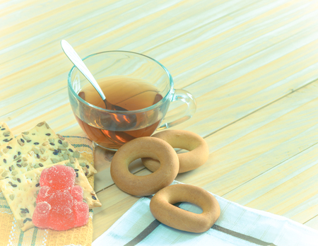 The composition of the tea beverage in a large bowl and some sweets on the table. Fruit jelly, cereal biscuits, bagel 版權商用圖片