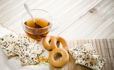table grain: The composition of the tea beverage in a large bowl and some sweets on the table. Grain cookies, bagel