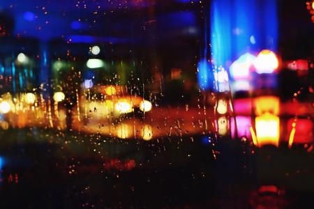 kropla deszczu: Zdjęcia nocne miasta wykonane przez szkło. Ulica. Deszcz. Bokeh Lights nieostry.