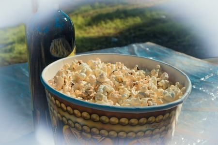 Camping. On the table, popcorn in a large glass and a bottle of wine. Against the background of blurred grass. 版權商用圖片