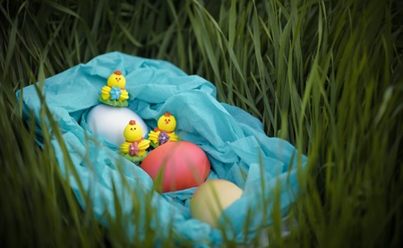Three toy chickens and three easter eggs on the grass in a blue basket. Composition.