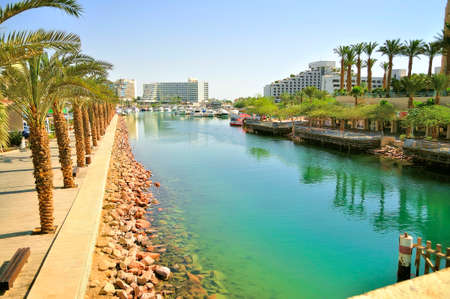 Photos from the bridge embankment on the dock in Eilat city. Canal to harbor when moored pleasure yachts and boats. Stock Photo