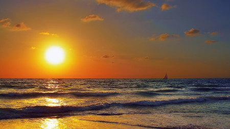 sun bathers: Golden landscape. The clouds, the waves, the sun and a sailboat in the distance