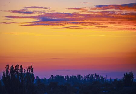 Evening landscape in the red-yellow-blue colors. Evening landscape in red, yellow and blue tones. Blur on the main elements. Stock Photo
