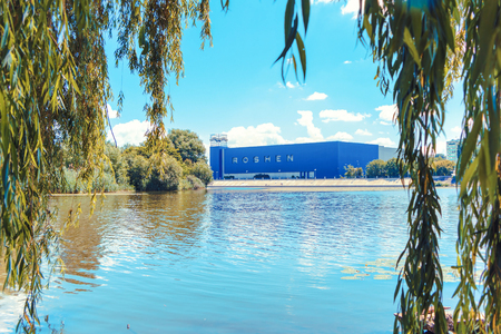 Roshen factory. The picture was taken in the shade of willow trees across the Southern Bug river on the island of Kemp and confectionery factory Poroshenko. Ukraine Editorial