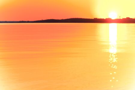 Uncomplicated evening sunset with beautiful sun glare on the water. A strip of coast on the horizon dark. Background blurred image.