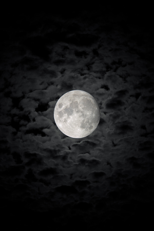 The detailed moon in the background of the cloudy night sky. Black and white. Vertical orientation. Stock Photo