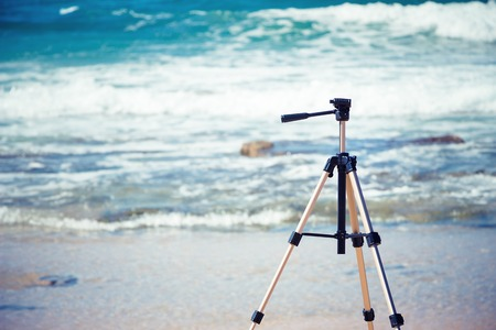 Tripod on the background of sea foam and waves. Device for the photographer Stock Photo