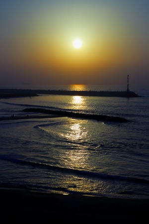 The lighthouse on the pier at sunset in the Mediterranean Sea. Landscape.