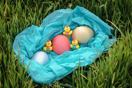 Three toy chickens and three easter eggs on the grass in a blue basket Stock Photo