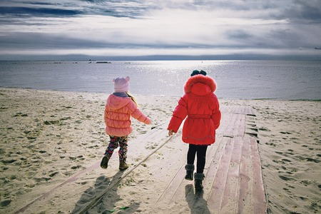 Two little girlfriends running to the sea after winter