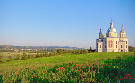 Holy temple on a hill with poppies against a clear sky.