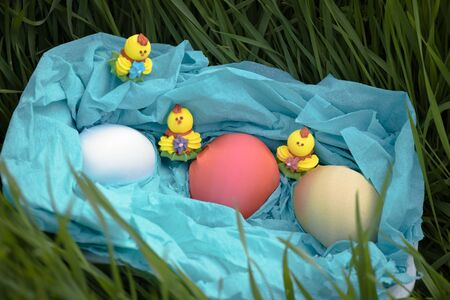 Three toy chickens and three easter eggs on the grass in a blue basket 版權商用圖片