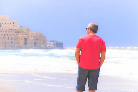 A man looks into the distance on the features of the Old City