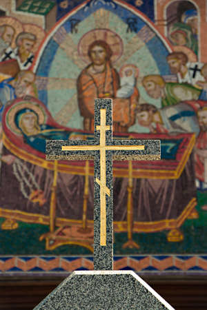 Small stone cross on the background of biblical mosaics