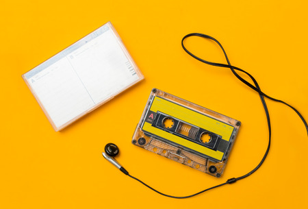 audio cassete and headphones, on yellow background