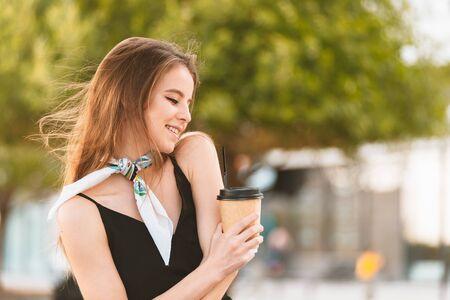 通りでコーヒーを飲む幸せな若い女性 写真素材