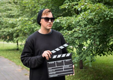 A man with clapperboard outdoor