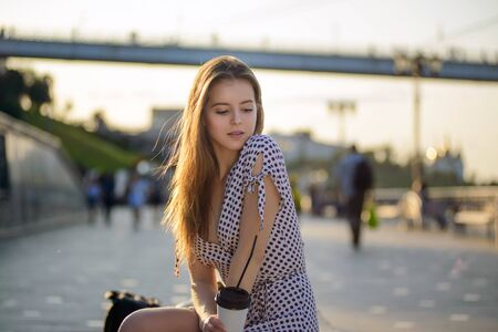 beautiful girl with coffee in hand sits on a bench on the street Stock Photo
