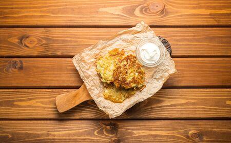 Potato pancakes with sour cream on a wooden background Reklamní fotografie