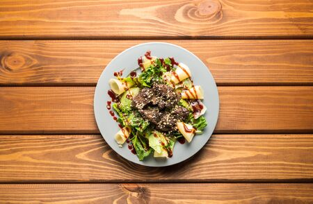 Salad with cheese, meat and herbs on a wooden background