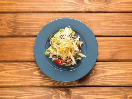 Salad chiken, tomatoes and herbs on a wood background