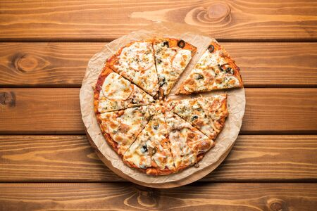 Pizza on wooden background. Top view