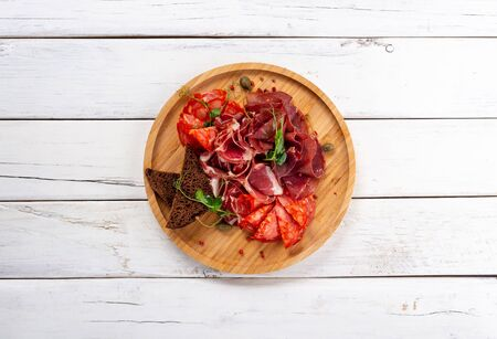 sliced bacon, meat and salami on a white wooden background