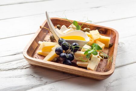 Plate with different types of cheese on white wood background Stock fotó