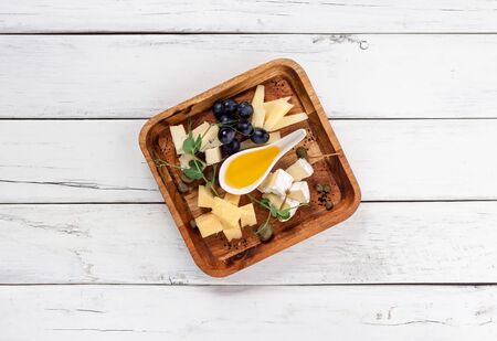 Plate with different types of cheese on white wood background Stock fotó - 136483909