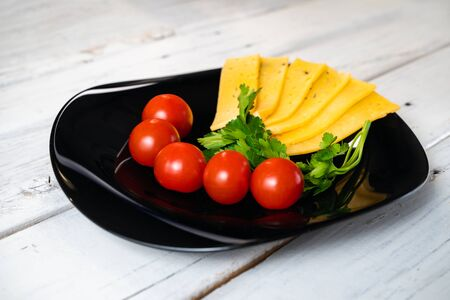 Slicing cherry tomatoes cheese on black plate on white wood