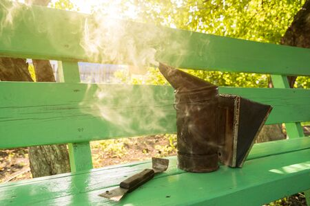 Beekeeping smoker and chisel on a bench Stock Photo