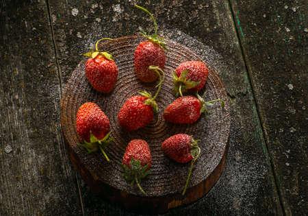 Strawberries on dark old wooden background